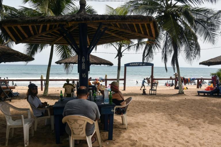 Life's a beach: Vacationers kick back at a hotel in Grand-Bassam. Tourism officials say coronavirus has badly hit numbers