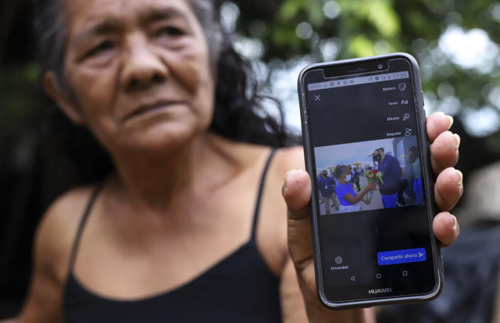 """Ines Flamenco holds up her smartphone showing a December 2020 photo of her presenting President Nayib Bukele with a bouquet of flowers, during an interview on her farm in Los Angelitos, El Salvador, Wednesday, July 28, 2021. Flamenco is one of a group of landslide survivors who have returned the homes given to them by the government. She said that if she had accepted she would been forced to abandon her farm animals. """"They took me to a place without asking and then accused me of being ungrateful for a gift that I didn't ask for."""" (AP Photo/Salvador Melendez)"""