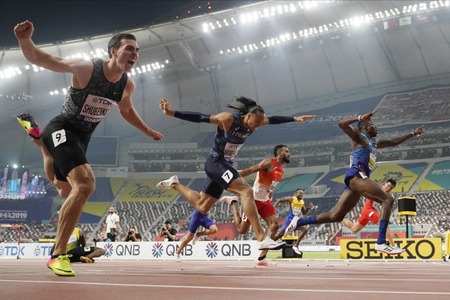 FILE - In this Oct. 2, 2019, file photo, Gold medallist Grant Holloway, of the United States, right, crosses the finish line ahead of Pascal Martinot-Lagarde, of France (7), and Orlando Ortega, of Spain (5), to win the men's 110 meter hurdles final at the World Athletics Championships in Doha, Qatar. At lower left is Jamaica's Omar Mcleod, who fell when clearing the last hurdle. The photo was part of a series of images by photographer David J. Phillip which won the Thomas V. diLustro best portfolio award for 2019 given out by the Associated Press Sports Editors during their annual winter meeting in St. Petersburg, Fla. (AP Photo/David J. Phillip, File)