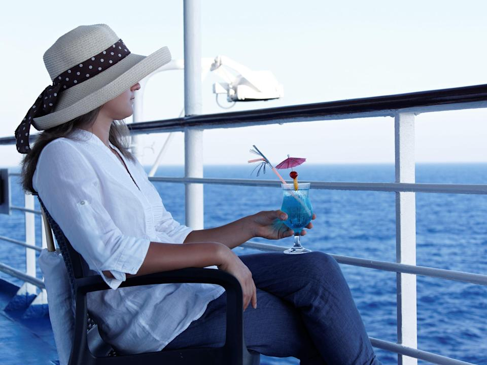 Woman sitting on the balcony of a cruise ship holding a tropical drink