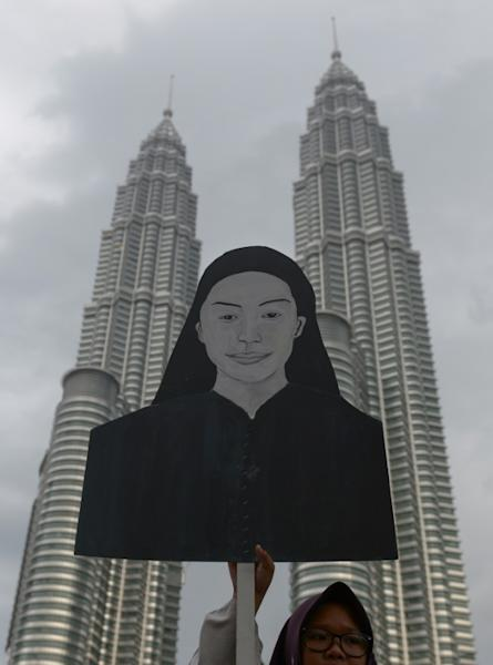 An Anwar supporter holds a cardboard figure of Mongolian model Altantuya Shaariibuu during a 2015 protest
