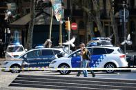 <p>Plain-clothes policemen phone as they walk past police cars in a cordoned off area after a van ploughed into the crowd, injuring several persons on the Rambla in Barcelona on August 17, 2017. (Josep Lago/AFP/Getty Images) </p>