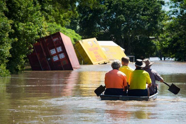 A group of workers paddle through floodwaters in a small boat to check on a house in Beenleigh, northeast Australia on March 31, 2017