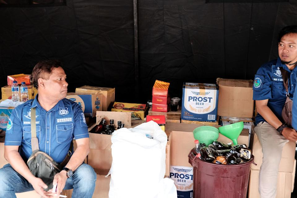 Photos show Indonesian police guards sitting with a stock of recently seized bootleg liquor in 2018.