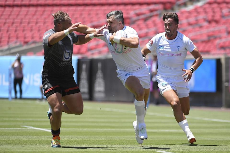 The Giltinis' Adam Ashley-Cooper tries to fend off a Rugby ATL player.