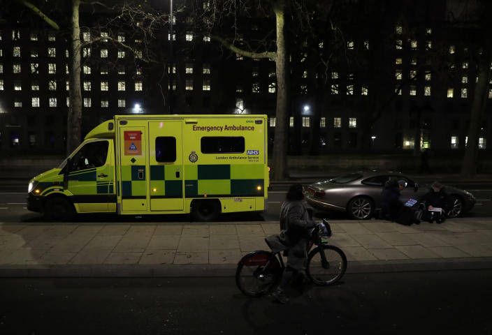 A woman with a bicycle walks past an ambulance and members of the media on the north bank of the River Thames opposite the London Eye ferris wheel by the River Thames in London, Thursday, Dec. 31, 2020. The London Eye is one of the traditional sites for New Year's Eve firework display, but it has been cancelled due to the ongoing coronavirus pandemic and the restrictions in place to try and stop its spread. (AP Photo/Matt Dunham)