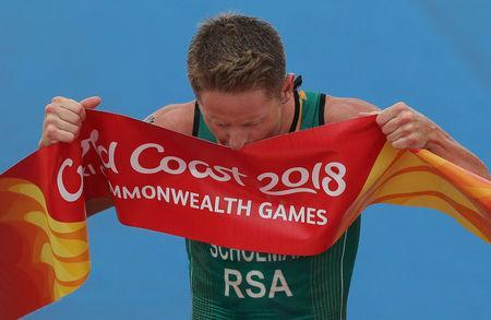Triathlon - Gold Coast 2018 Commonwealth Games - Men's Final - Southport Broadwater Parklands - Gold Coast, Australia - April 5, 2018 - Henri Schoeman of South Africa kisses the finish line ribbon after winning the event. REUTERS/Athit Perawongmetha