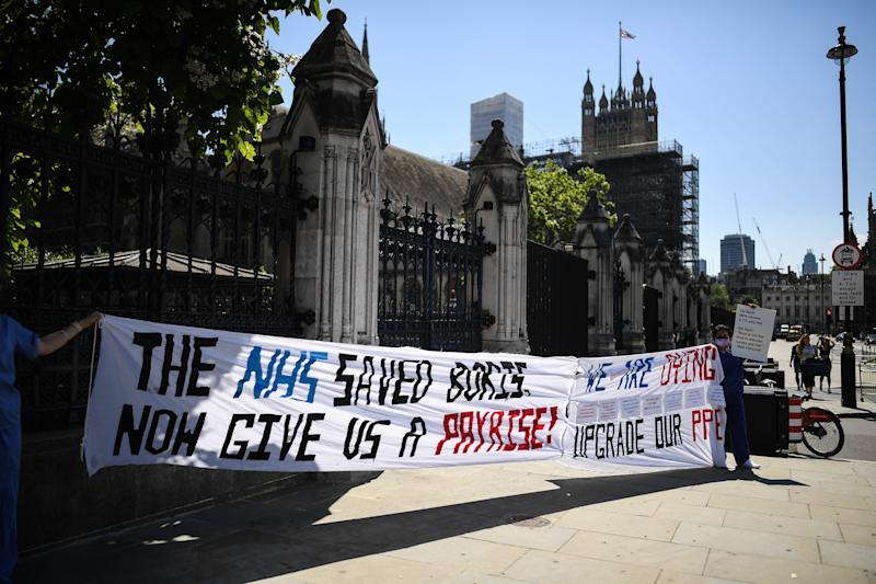 """LONDON, ENGLAND - JUNE 25: NHS workers are seen holding a banner reading """"The NHS saved Boris, now give us a pay rise"""" outside the Houses of Parliament on June 25, 2020 in London, England. British Prime Minister Boris Johnson was admitted to hospital in April after contracting Coronavirus. (Photo by Peter Summers/Getty Images)"""