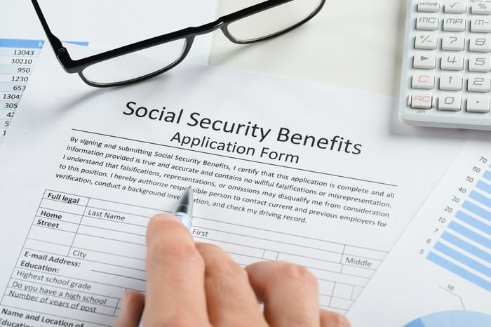 A person filling out a Social Security benefit application.