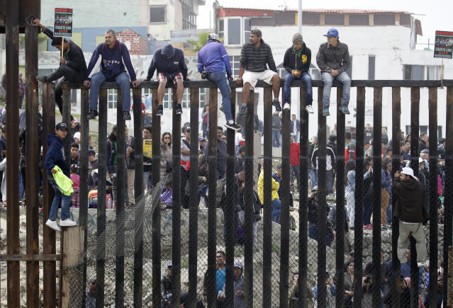 <p>Central American migrants sit on top of the border wall on the beach during a gathering of migrants living on both sides of the border, April 29, 2018, in San Diego. (Photo: Chris Carlson/AP) </p>