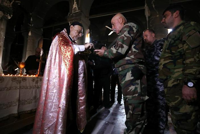 Archbishop of Mosul Yohanna Petros Mouche gives communion to Iraqi Christian forces as he leads a mass at the Church of the Immaculate Conception on October 30, 2016 in the town of Qaraqosh after Iraqi forces recaptured it from the Islamic State (AFP Photo/Safin Hamed)