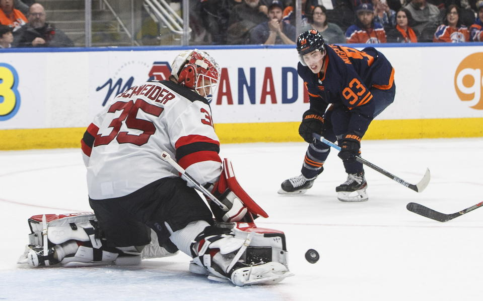New Jersey Devils goalie Cory Schneider (35) makes the save on Edmonton Oilers' Ryan Nugent-Hopkins (93) during the second period of an NHL hockey game Friday, Nov. 8, 2019, in Edmonton, Alberta. (Jason Franson/The Canadian Press via AP)