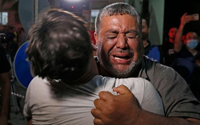 A Palestinian man cries at a hospital in Gaza City City, where those injured or killed in Israeli air strikes are transferred, on, May, 12, 2021 - ANAS BABA/AFP