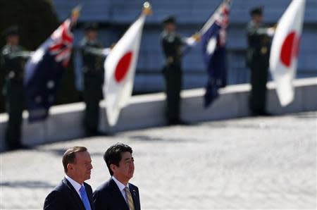 Australia's PM Abbott reviews a guard of honour with Japan's PM Abe during a welcome ceremony hosted by Abe at the state guest house in Tokyo