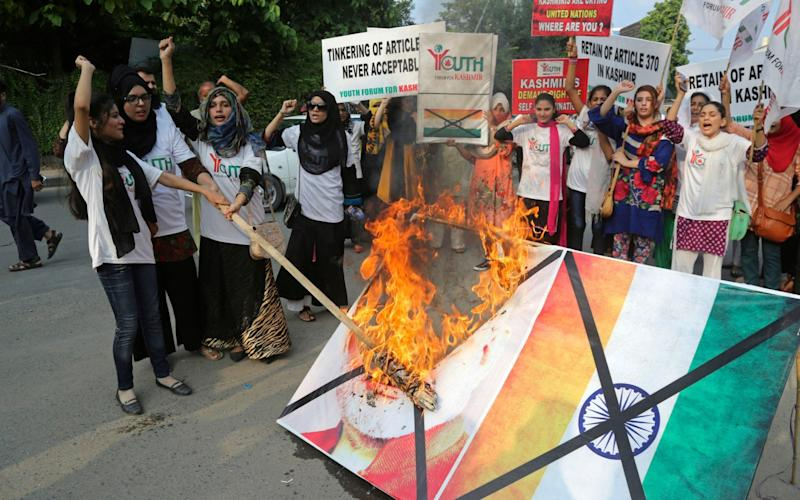 Pakistani students burn a poster of Indian Premier Narendra Modi during an anti-Indian rally in Lahore, Pakistan - AP