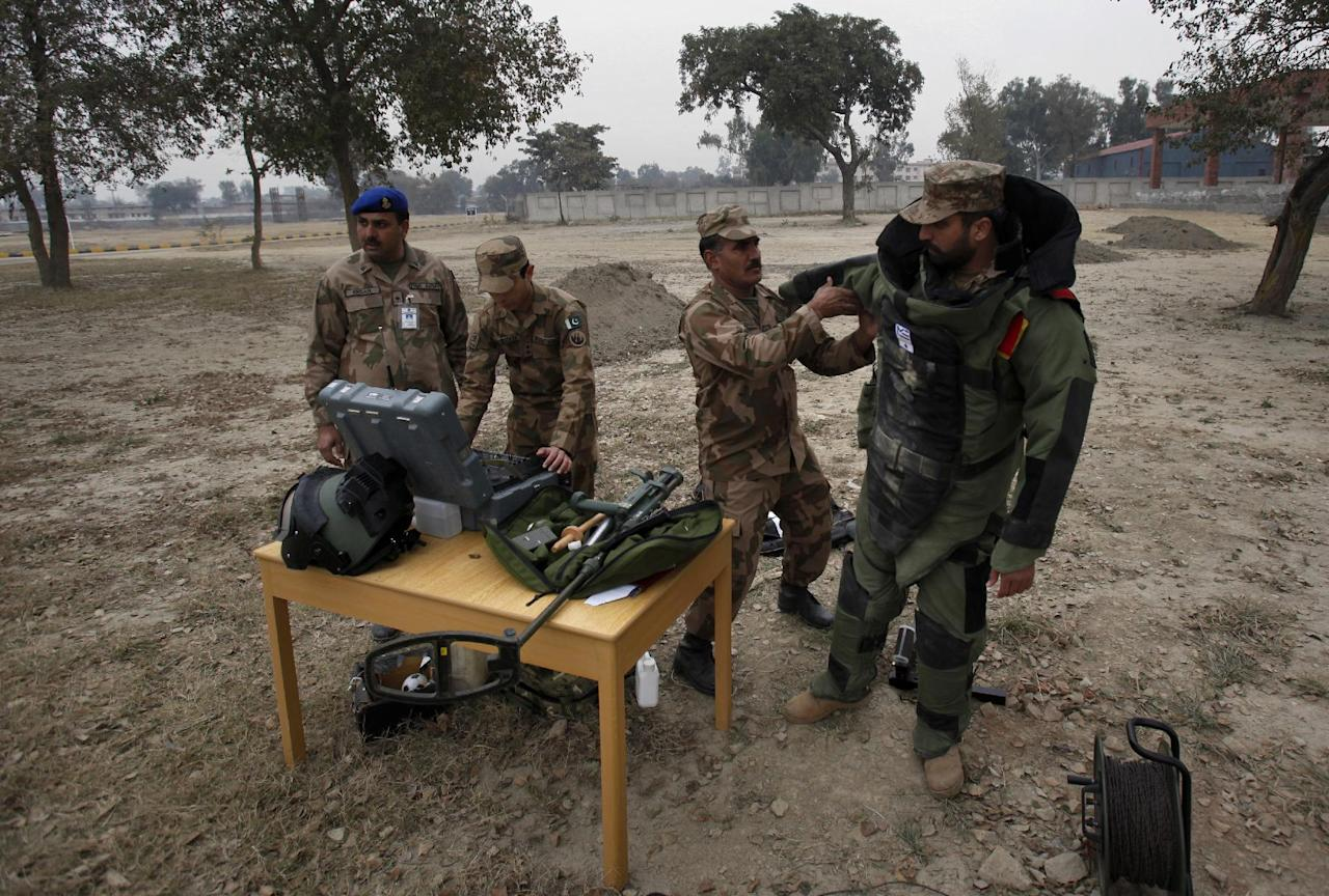 In this Wednesday, Jan. 8, 2014, photo, A Pakistani soldier helps his colleague to put on a bomb suit for a training session at the Counter IED Explosives and Munitions School, in Risalpur, Pakistan. Militants in Pakistan have become devilishly ingenious about where they plant improvised explosive devices, a type of bomb responsible for thousands of wounds and deaths in Pakistan. They've been found strapped to children's bicycles, hidden inside water jugs and even hung in tree branches. (AP Photo/Anjum Naveed)