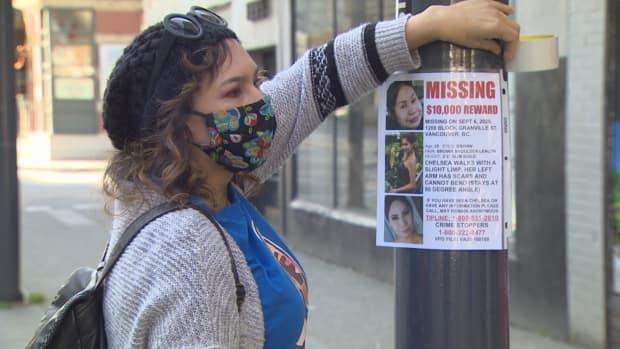 Sheila Poorman puts up posters of her daughter on Vancouver's Granville Street, where she went missing.  (CBC/Ken Leedham - image credit)