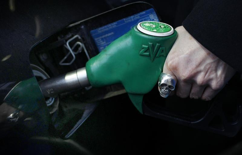 A woman fuels her car at a petrol station in London