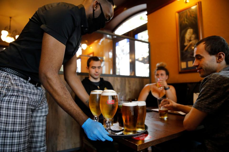 A member of bar staff wearing PPE (personal protective equipment) in the form of golves and a face mask, serves seated customers with drinks inside the Wetherspoon pub, Goldengrove in Stratford in east London on July 4, 2020, as restrictions are further eased during the novel coronavirus COVID-19 pandemic. - Pubs in England reopen on Saturday for the first time since late March, bringing cheer to drinkers and the industry but fears of public disorder and fresh coronavirus cases. (Photo by Tolga AKMEN / AFP) (Photo by TOLGA AKMEN/AFP via Getty Images)