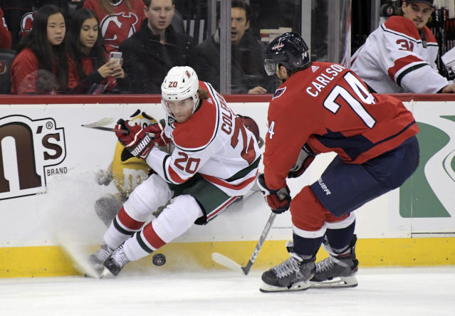 New Jersey Devils center Blake Coleman (20) and Washington Capitals defenseman John Carlson (74) vie for the puck during the second period of an NHL hockey game Friday, Dec. 20, 2019, in Newark, N.J. (AP Photo/Bill Kostroun)