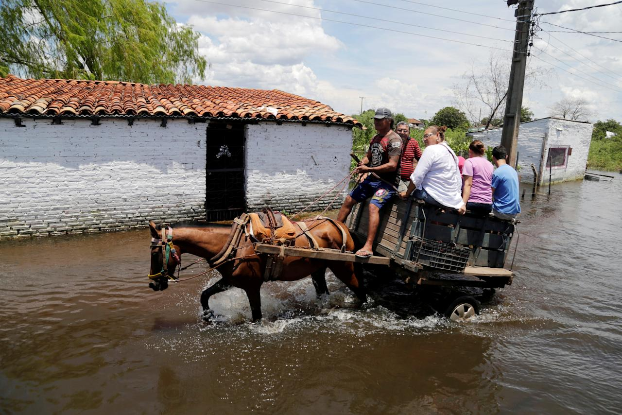 People ride on a horse carriage through a flooded street after heavy rains caused the river Paraguay to overflow, in Asuncion, Paraguay January 22, 2018.    REUTERS/Jorge Adorno     TPX IMAGES OF THE DAY