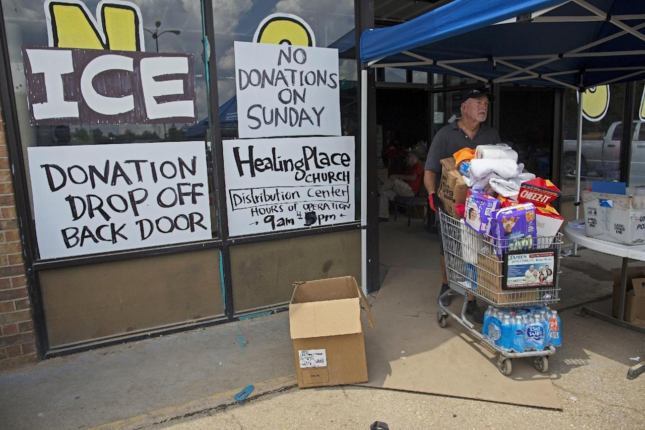 Volunteer Randy Fowler pushes a basket full of donated goods being given to flood victims as part of the emergency aid operations of Healing Place Church in Denham Springs, La., Wednesday, Aug. 24, 2016. Volunteers have served thousands of free meals and passed out carloads of clothes, food, cleaning supplies and other essentials. (AP Photo/Max Becherer)