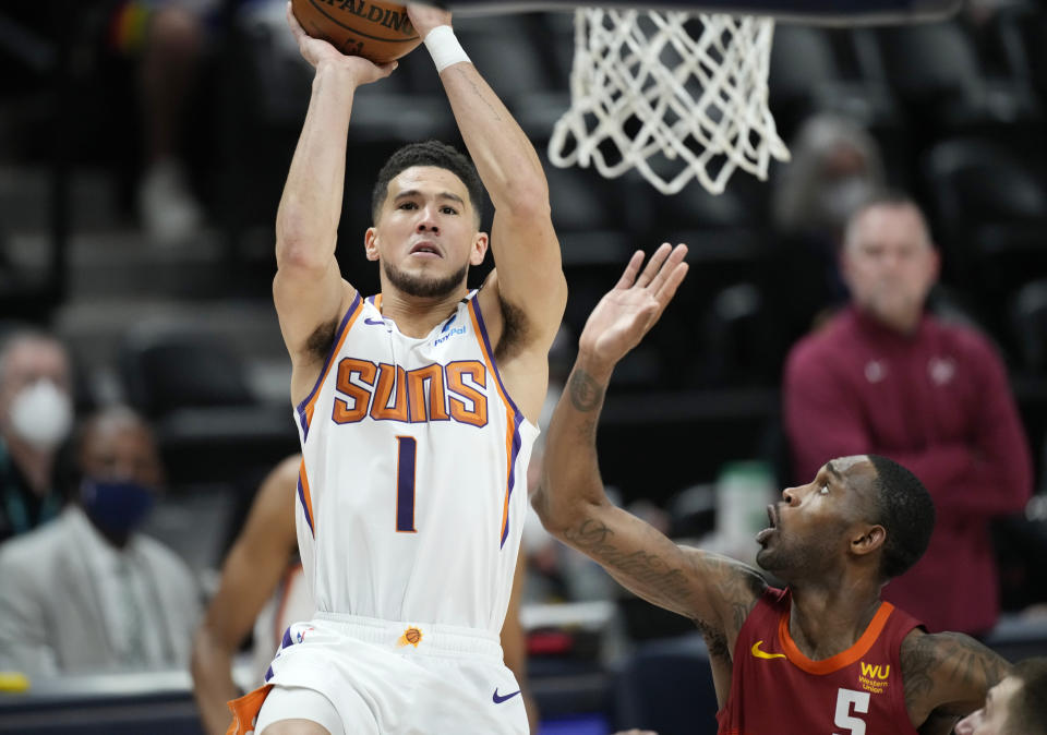 Phoenix Suns guard Devin Booker, left, goes up for a basket as Denver Nuggets forward Will Barton defends in the first half of Game 4 of an NBA second-round playoff series Sunday, June 13, 2021, in Denver. (AP Photo/David Zalubowski)