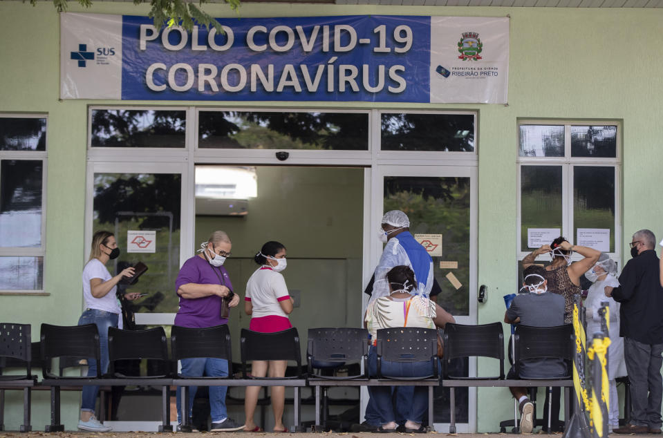 People with COVID-19 symptoms wait to be assisted outside a hospital that is at full capacity in Ribeirao Preto, Sao Paulo state, Brazil, Friday, May 28, 2021. The city imposed strict shutdown measures this week to stop the spread of the virus, halting public transportation for the first time and closing supermarkets. (AP Photo/Andre Penner)