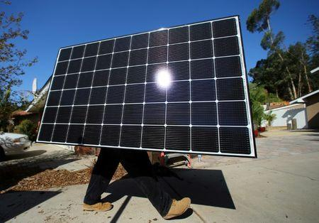 A solar installer carries a solar panel during an installation  at a residential home in Scripps Ranch, San Diego