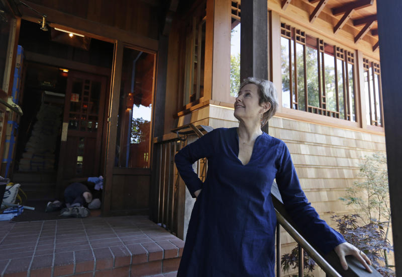In this photo taken Thursday, June 20, 2013 Alice Waters looks over the new front entrance to her Chez Panisse restaurant in Berkeley, Calif. After a fire in March shut the doors to the famous gourmet restaurant, the eatery is preparing to reopen June 24. (AP Photo/Eric Risberg)
