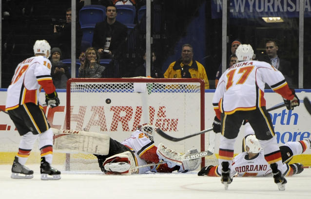 Calgary Flames goalie Reto Berra (29) falls to the ice as he deflects a puck away from the goal shot by New York Islanders in the first period of an NHL hockey game, Thursday, Feb. 6, 2014, in Uniondale, N.Y. (AP Photo/Kathy Kmonicek)