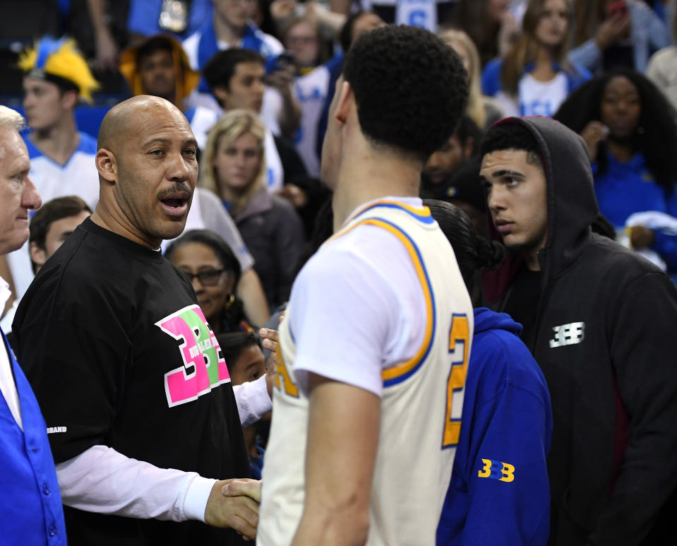 """In this March 4, 2017, file photo, UCLA guard Lonzo Ball, right, shakes hands with his father LaVar following an NCAA college basketball game against Washington State in Los Angeles. UCLA won 77-68. LaVar Ball told Southern California News Group for a story published online on April 6, 2017, that UCLA was eliminated in the NCAA tournament because """"three white guys"""" couldn't pick up the slack after his son suffered a hamstring injury. (AP Photo/Mark J. Terrill, File)"""