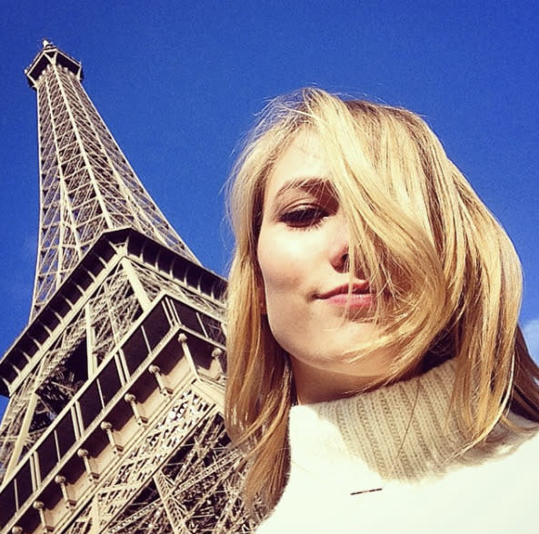 """Repeat poser! In 2015, Karlie wrote, """"Bonjour Paris,"""" on this pic of her posing beneath it again while rocking messy bangs. (Photo: Karlie Kloss via Instagram)"""