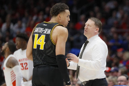 Virginia Commonwealth's Marcus Santos-Silva (14) speaks with coach Mike Rhoades, right, during the first half of an NCAA college basketball game against Dayton Tuesday, Jan. 14, 2020, in Dayton, Ohio. (AP Photo/John Minchillo)