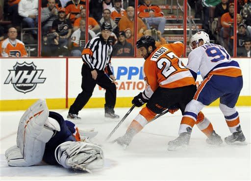 New York Islanders goalie Evgeni Nabokov, left, goes down on the ice to block the shot of Philadelphia Flyers' Max Talbot, center, as Islanders' John Tavares trails the play during the second period of an NHL hockey game, Tuesday, Feb. 7, 2012, in Philadelphia. (AP Photo/Tom Mihalek)