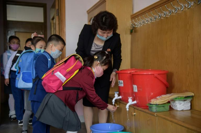 North Korean children wash their hands before taking their seats at a primary school in Pyongyang