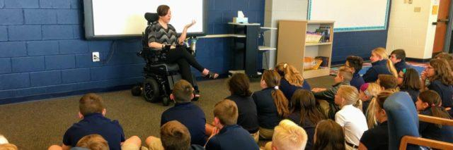 Marie in her wheelchair speaking to a group of sixth graders.