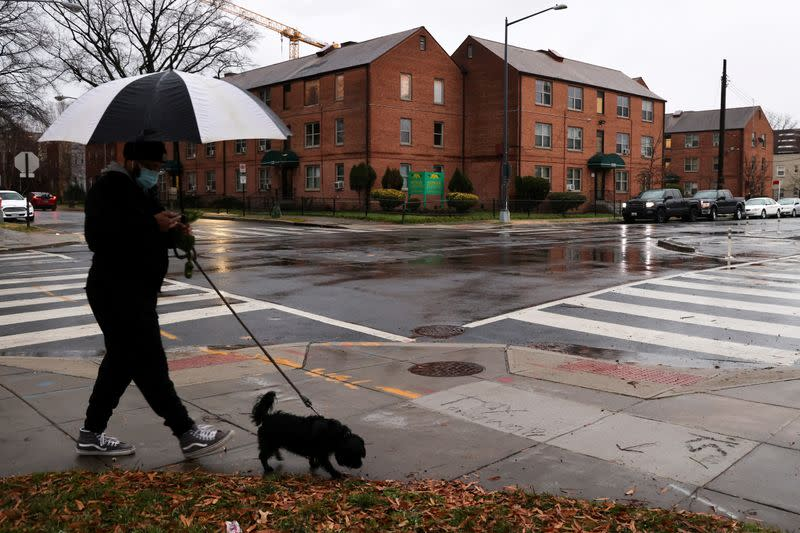 A resident walks their dog near the home Woody and her grandson share in Washington