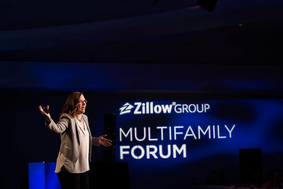 Person speaking on stage with a backdrop showing Zillow Group Multifamily Forum.