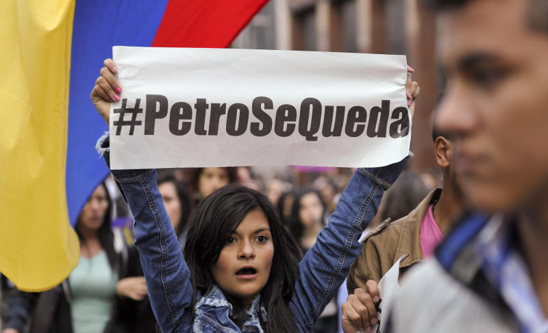 """A supporters of Bogota's Mayor Gustavo Petro holds a sign that reads in Spanish: """"Petro Stays,"""" during a rally against Colombia's inspector-general Alejandro Ordonez in Bogota, Colombia, Friday, Dec. 13, 2013. Ordonez has ordered Petro removed from office over alleged mismanagement of the garbage-collection system. (AP Photo/Carlos Julio Martinez)"""