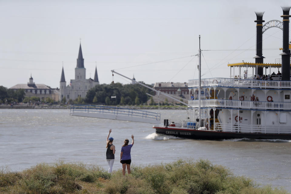 In this July 25, 2019 photo, Roxanne Taylor, right, and Brigitte Blanchard, wave to a paddlewheel boat from a levee revetment on Algiers Point in New Orleans, with the French Quarter and St. Louis Cathedral seen in the background. The river that drains much of the flood-soaked United States is running far higher than normal this hurricane season, menacing New Orleans in multiple ways. One continuing concern is the massive volume of water that for months has been pushing against levees protecting a city that's mostly below sea level. (AP Photo/Gerald Herbert)