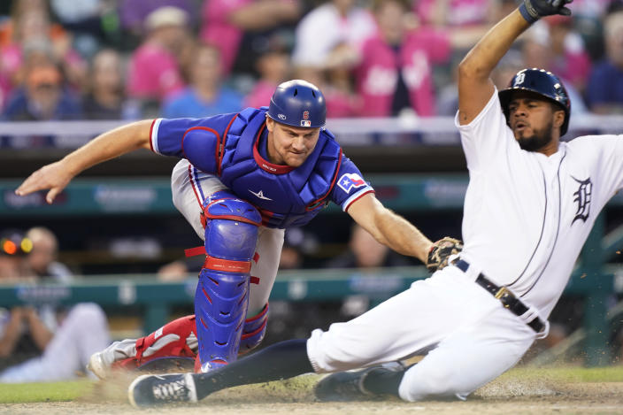 Texas Rangers catcher John Hicks (6) tags out Detroit Tigers' Jeimer Candelario during the sixth inning of a baseball game, Wednesday, July 21, 2021, in Detroit. Candelario was attempting to score from second on a single by teammate Harold Castro to left field. (AP Photo/Carlos Osorio)