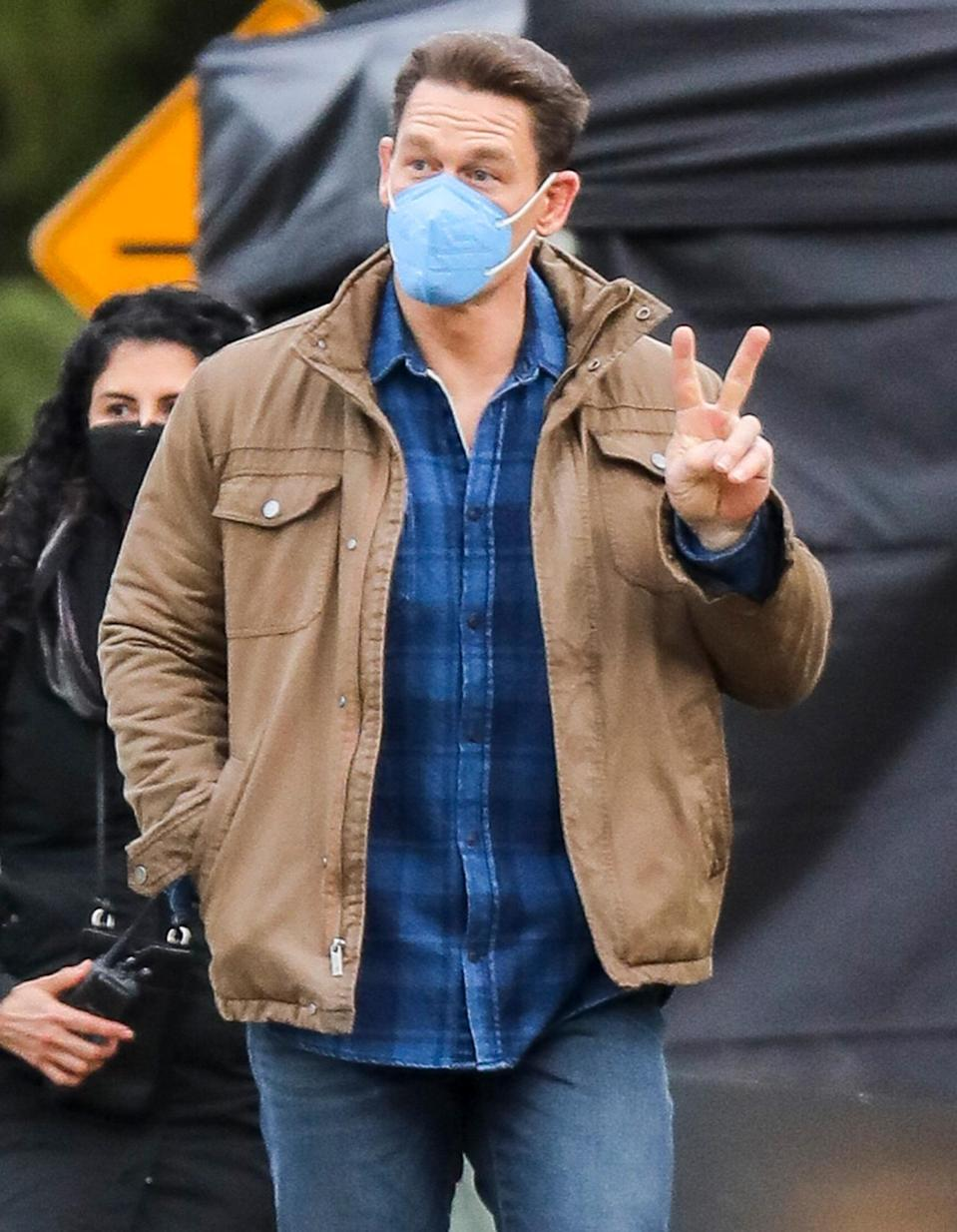 <p>John Cena flashes a peace sign on the set of <em>The Peacemaker</em> on Tuesday in Vancouver.</p>