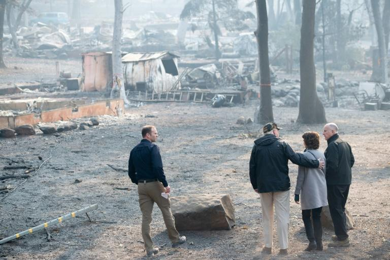 US President Donald Trump (C) hugged Paradise Mayor Jody Jones (2R) while surveying the remains of the California town of Paradise