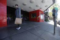 A pedestrian walks past a closed CineArts Empire theater in San Francisco