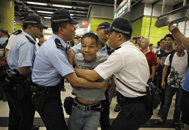 Police restrain an angry passenger who tried to fight with protesters in Hong Kong on Tuesday, July 30, 2019. Protesters in Hong Kong have disrupted subway service during the morning commute by blocking the doors on trains, preventing them from leaving the stations. (AP Photo/Vincent Yu)