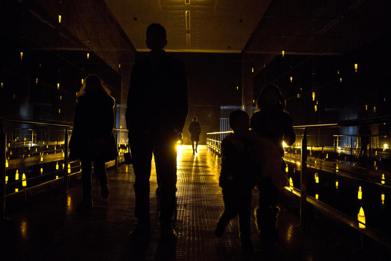 In this Feb. 11, 2014 photo, visitors walk through a hall filled with yellow bulbs symbolizing massacre victims at Nanjing Massacre Memorial Hall in Nanjing, in eastern China's Jiangsu province. The Tokyo shrine and the memorial hall in Nanjing, as Nanking is now called, are physical embodiments of divergent views of history that still strain China-Japan relations, 70 years after the war. They complicate America's objective of maintaining peace and stability in the Pacific, as President Barack Obama starts a 4-country Asian tour in Japan this week. The implications are potentially serious, particularly over contested uninhabited islands called the Senkaku by Japan and Diaoyu by China. (AP Photo/Alexander F. Yuan)