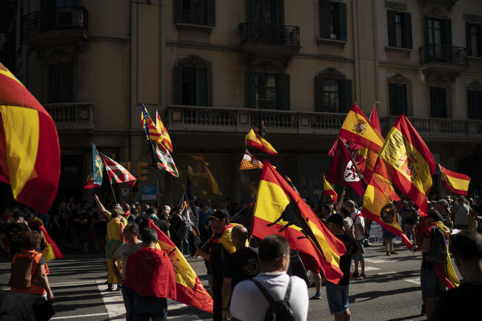 Members and supporters of National Police and Guardia Civil wave Spanish flags during a protest demanding better pay in Barcelona, Spain, Saturday, Sept. 29, 2018. (AP Photo/Felipe Dana)