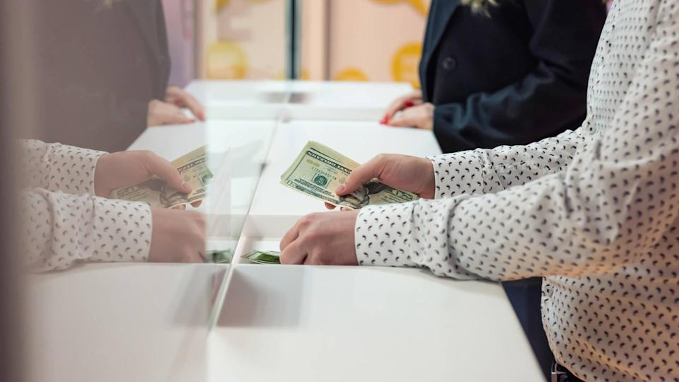 Male hand with money at cash desk.