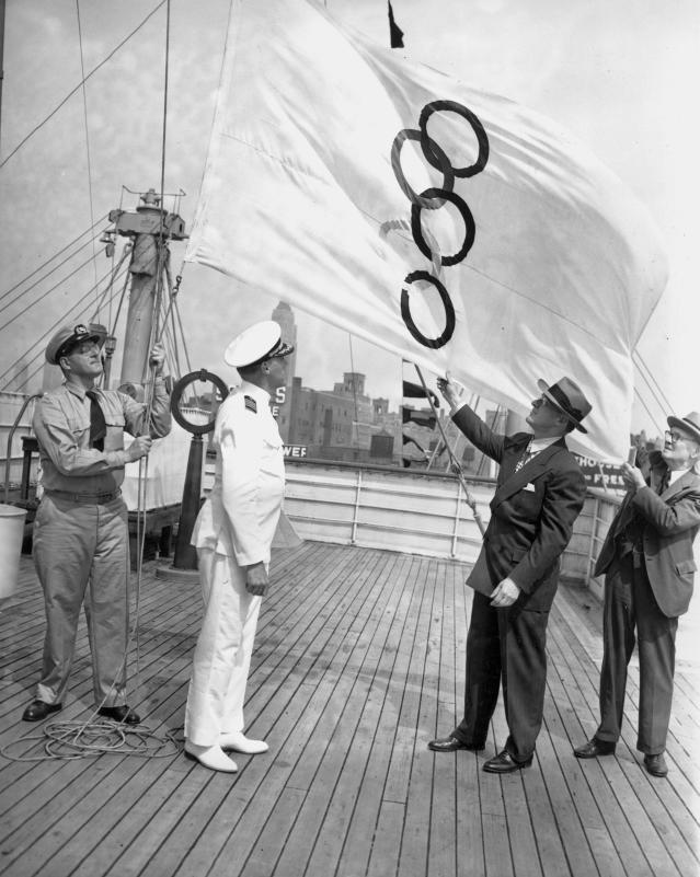 The Olympic flag is hoisted by quartermaster Richardson C. Bang, left, on the liner America in New York City, July 14, 1948. The ship is sailing for London, England, with 260 athletes and 44 coaches of the United States Olympic teams for the Summer Olympic Games. Capt. John W. Anderson of the America, center, and Avery Brundage, second from right, President of the U.S. Olympic Committee, assist in the proceedings. Note the five interlocked rings are vertical on the white flag. (AP Photo)